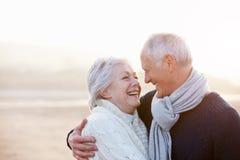 Romantiska höga par på vinterstranden royaltyfria bilder
