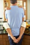 Romantiska höga par som kramar i kök Royaltyfri Fotografi