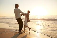 Romantiska höga par som tycker om en dag på stranden Royaltyfri Foto