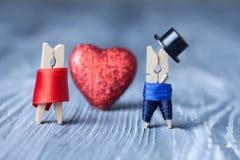 Romantiska klädnypor red steg Man kvinna klädnypor Gentleman i svart hatt och kvinna i röd klänning Arkivbilder