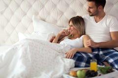 Romantiska lyckliga par som har frukosten i säng Royaltyfria Bilder