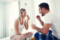 Romantiska lyckliga par som har frukosten i säng Arkivbilder