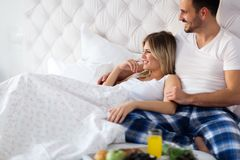 Romantiska lyckliga par som har frukosten i säng arkivfoto