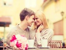 Romantiska lyckliga par som kysser i kafét Arkivbilder