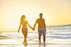 Romantiska par för bröllopsresa som är förälskade på strandsolnedgången royaltyfria bilder