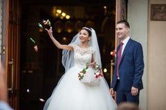 Romantiska par för lycklig nygift person som kommer ut ur kyrka efter weddin royaltyfria foton