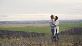 Romantiska par i embracess och kyssar står på överkanten av vaggar arkivfilmer