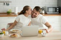 Romantiska par kysser att tycka om den läckra sunda frukosten på hom royaltyfri foto