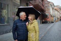 Romantiska par med ?lderskillnaden som till varandra ser med lycka och ler p? anseende under deras paraply royaltyfri bild