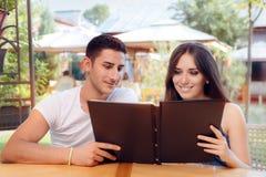 Romantiska par på en hållande restaurangmeny för datum royaltyfria bilder