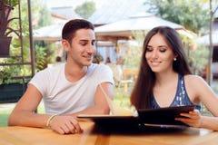 Romantiska par på en hållande restaurangmeny för datum arkivbild