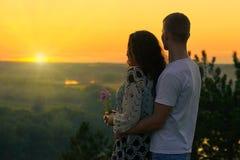 Romantiska par ser på solen, afton på det utomhus- härliga landskapet och ljus gul himmel, förälskelsemjukhetbegreppet, ung vuxen Arkivfoton