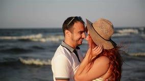 Romantiska par som är kyssande och kramar på stranden under solnedgång Slappa soliga färger See är i bakgrunden stock video
