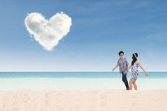 Romantiska par som går på stranden Arkivfoto