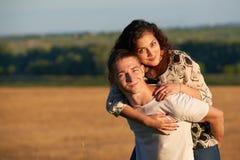 Romantiska par som har gyckel på wheaten fältbakgrund på solnedgången, sommarsäsong, flickaridning på manbaksida Arkivbild