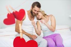 Romantiska par som hemma ser graviditetstestet i sovrum arkivfoton