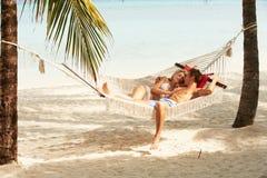 Romantiska par som kopplar av i strandhängmatta Arkivbilder