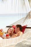 Romantiska par som kopplar av i strandhängmatta Arkivfoton