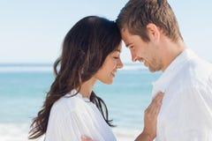 Romantiska par som kopplar av och omfamnar på stranden royaltyfri fotografi