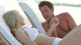Romantiska par som kopplar av på dagdrivare på stranden arkivfilmer