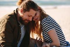 Romantiska par som kopplar av på stranden royaltyfria bilder