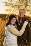 Romantiska par som kramar höstsolnedgångbygd arkivbild