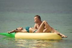 Romantiska par som ligger på säng Mannen och kvinnan på bröllopsresa, bad på ananas formade madrassen i havet lyckligt barn för p Arkivfoton