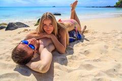 Romantiska par som ligger på stranden Royaltyfri Foto
