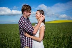 Romantiska par som omfamnar sig i fält Arkivbild