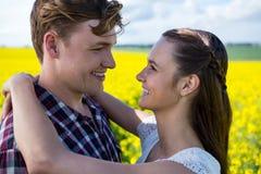 Romantiska par som omfamnar sig i senapsgult fält Royaltyfri Bild