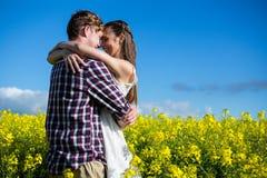 Romantiska par som omfamnar sig i senapsgult fält Royaltyfria Bilder