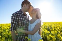 Romantiska par som omfamnar sig i senapsgult fält Arkivbilder