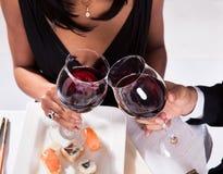 Romantiska par som rostar rött vin Arkivbild