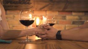 Romantiska par som rymmer händer på tabellen med stearinljus och vinexponeringsglas Man och kvinna som rymmer händer på det roman stock video