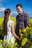 Romantiska par som ser de i senapsgult fält Royaltyfri Bild