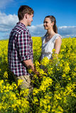 Romantiska par som ser de i senapsgult fält Arkivfoto