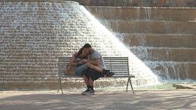 Romantiska par som sitter på bänken nära springbrunnen på Riverwalk i San Antonio royaltyfri bild