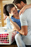Romantiska par som sorterar tvätterit i kök Fotografering för Bildbyråer
