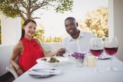 Romantiska par som tillsammans sitter i restaurang Arkivbilder