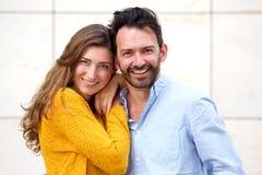 Romantiska par som tillsammans står, i att le för omfamning arkivbild