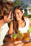 Romantiska par som tycker om drinkar på strandklubban Arkivfoto