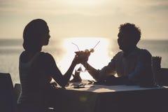 Romantiska par tycker om solnedgång i restaurang på stranden som dricker coctailar Arkivbild
