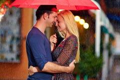 Romantiska par under regnet på aftongatan Royaltyfri Fotografi