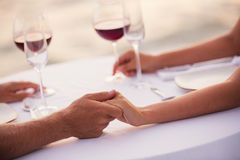 Romantiska parinnehavhänder på matställen Royaltyfri Bild