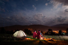 Romantiska parturister som sitter vid brasan under molnig himmel Royaltyfri Foto