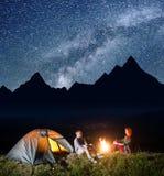 Romantiska parturister som sitter vid lägereld och tältet under incredibly härlig stjärnklar himmel och till varandra ser Arkivfoton