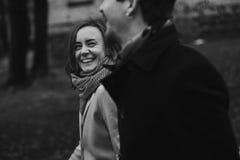 Romantiska stilfulla par som går och skrattar i höst, parkerar man Arkivbilder