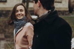 Romantiska stilfulla par som går och skrattar i höst, parkerar man Royaltyfri Bild