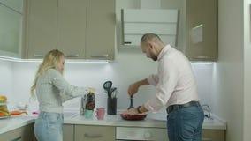 Romantiska tillfälliga par som gör frukosten i kök arkivfilmer