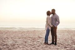Romantiska unga afrikanska par som kysser på en strand på skymning arkivbilder
